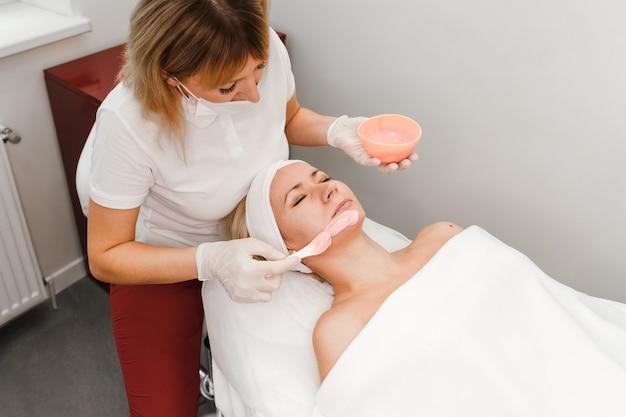 La cosmetóloga aplica una máscara en la cara del cliente.