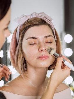 Cosmetóloga aplicando base sobre mujer