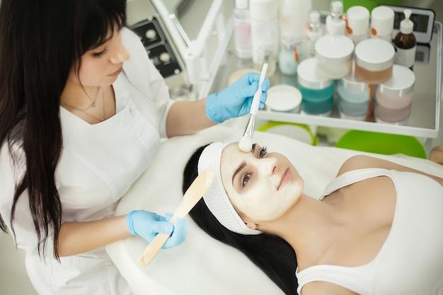 Cosmetóloga aplicando crema facial al cliente en la oficina de cosmetología
