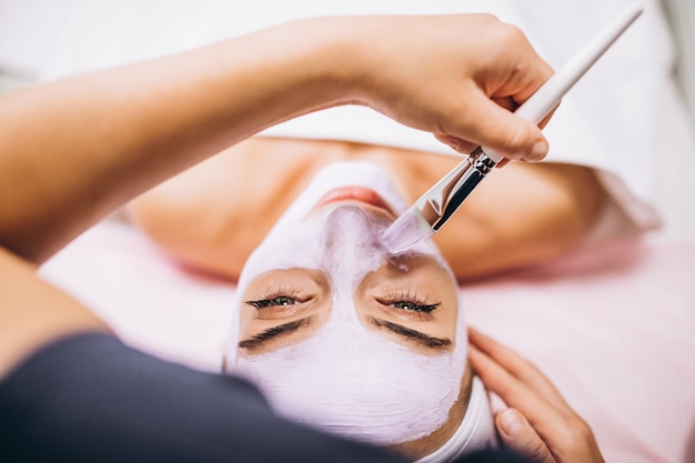 Cosmetóloga aplicando una máscara en la cara del cliente en un salón de belleza
