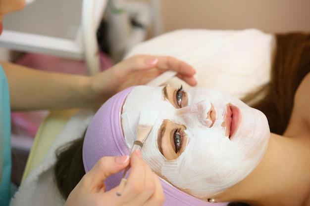 Cosmetóloga aplicando máscara facial en salón de belleza.