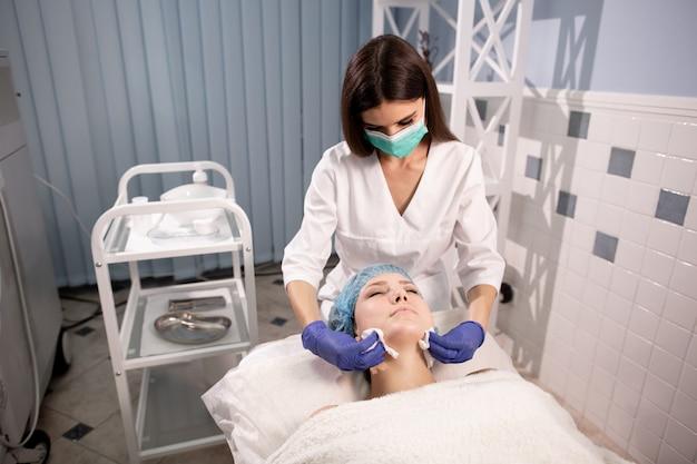 La cosmetóloga con guantes azules limpia la cara del paciente antes de los procedimientos cosméticos