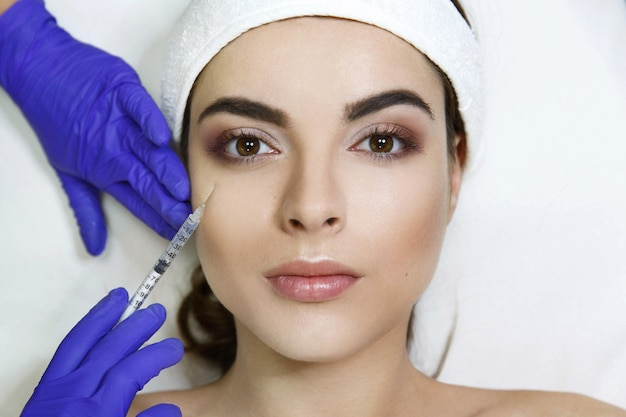 Cosmetóloga hace inyección de belleza en la cara de la mujer en la clínica