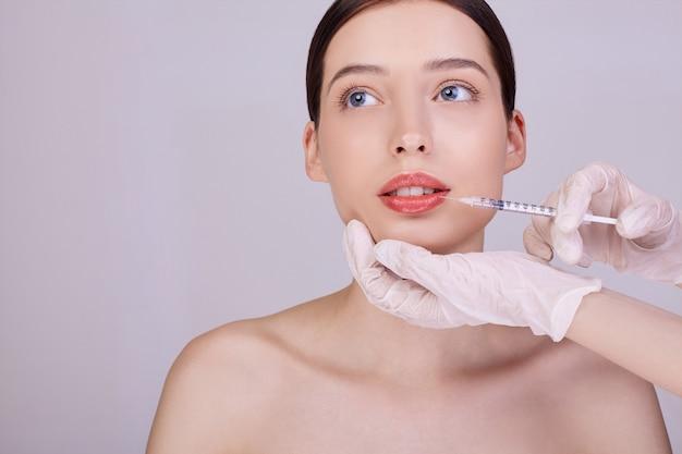 Cosmetóloga hace procedimientos para labios mujer
