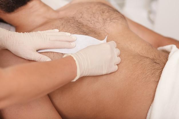 Cosmetóloga haciendo depilación con cera en el torso del cliente masculino