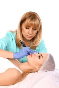 Cosmetóloga haciendo maquillaje permanente en los labios de la mujer.