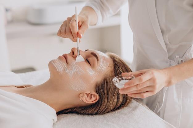 Cosmetóloga haciendo tratamiento facial y aplicando mascarilla