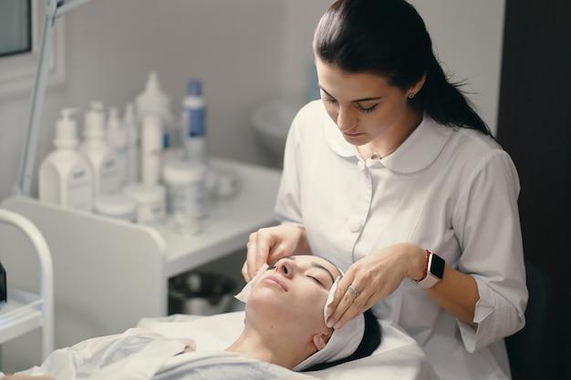 Cosmetóloga haciendo tratamiento facial a una bella mujer