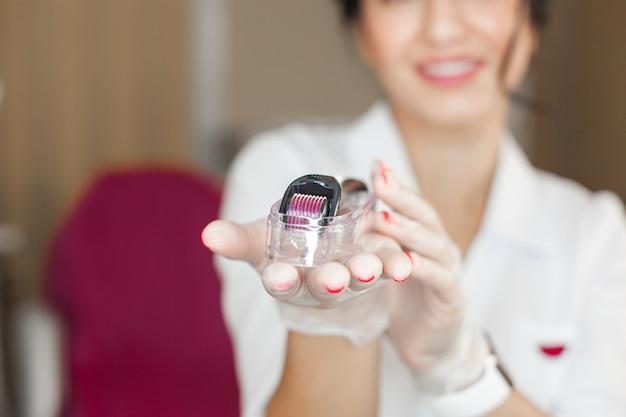 Cosmetóloga joven atractiva con un mesoroller en sus manos. ciérrese encima del retrato del dermatólogo con su equipo. especialista en mesoterapia en la clínica.