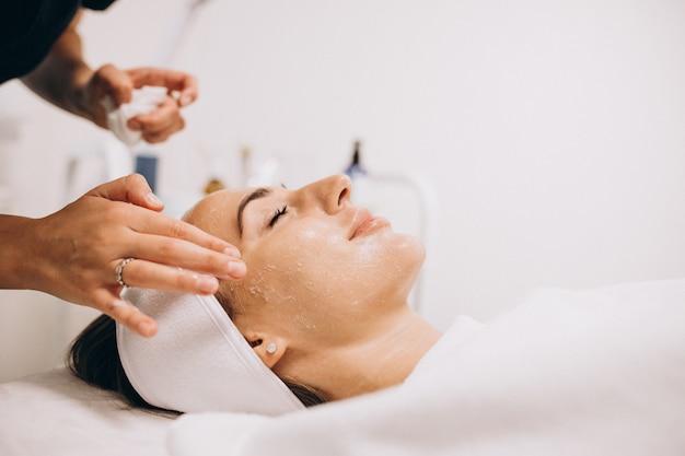 Cosmetóloga limpiando la cara de una mujer en un salón de belleza