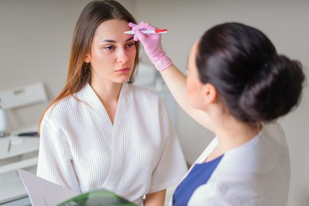 Cosmetóloga lista para pintar líneas con marcador en la cara del paciente