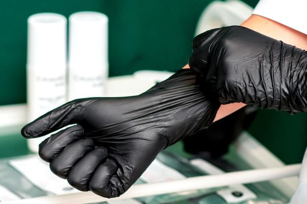 La cosmetóloga lleva guantes negros de látex en sus manos, de cerca.