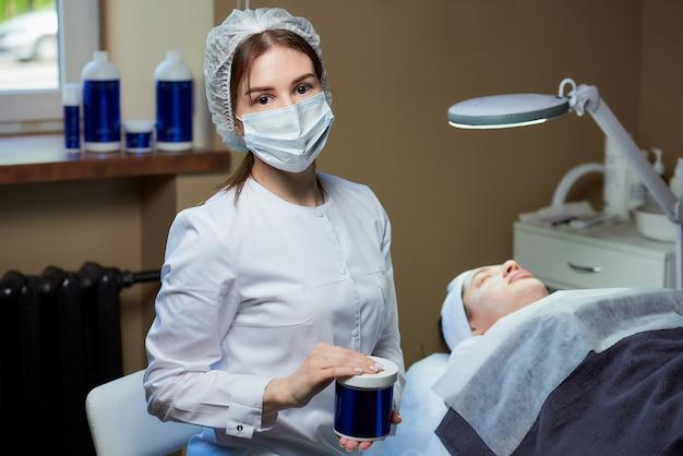 Una cosmetóloga en una máscara posando con un producto para el cuidado de la piel cerca de un paciente