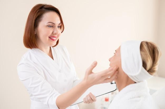 Cosmetóloga pelirroja sonriente con portapapeles comprobando la piel de la cara del cliente maduro antes del procedimiento cosmético