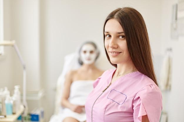 Cosmetóloga posa en su gabinete con su cliente
