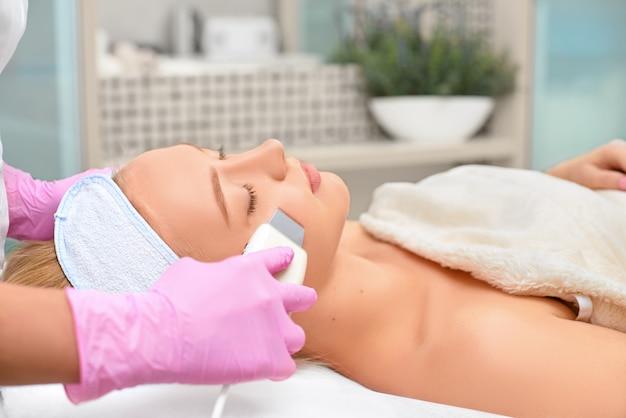 Cosmetóloga de primer plano haciendo limpieza de hardware de ultrasonido de la cara de su paciente una hermosa mujer joven, concepto de limpieza de la piel y restauración de la elasticidad