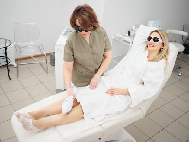 La cosmetóloga realiza la depilación en la pierna del paciente.