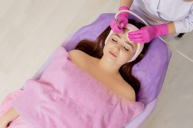 La cosmetóloga realiza el procedimiento microdermoabrasión de la piel facial de una bella y joven mujer en un salón de belleza.cosmetología y cuidado profesional de la piel.