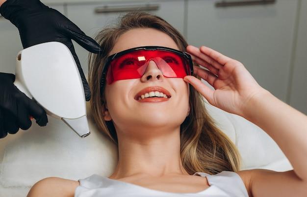 Cosmetóloga realizando depilación láser a su cliente.