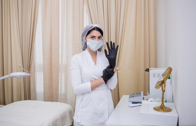 Cosmetóloga con uniforme blanco se pone guantes desechables negros en la oficina