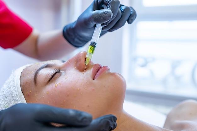 Cosmetología de hardware, mesoterapia, retrato de una mujer joven que recibe tratamiento de la zona de la frente