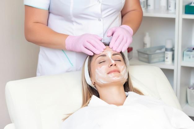 Cosmetología. mujer joven con recibir procedimiento de limpieza facial en salón de belleza.