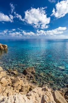 Costa del mar con agua turquesa clara y piedras afiladas en el cabo cavo greco, chipre. marco vertical