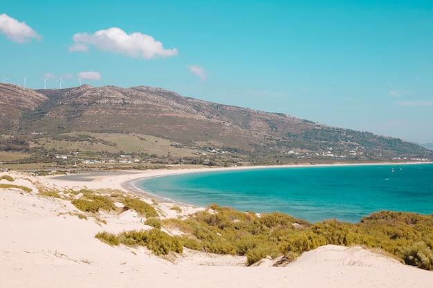 Costa del mar con colinas y mar azul.