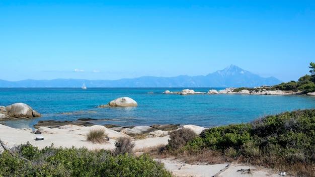 Costa del mar egeo con gente nadando, rocas sobre el agua y tierra con barco en la distancia, vegetación en primer plano, agua azul, grecia