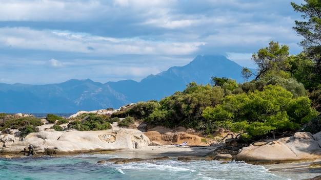 Costa del mar egeo con vegetación alrededor, rocas, arbustos y árboles, agua azul con olas, montaña que llega a las nubes