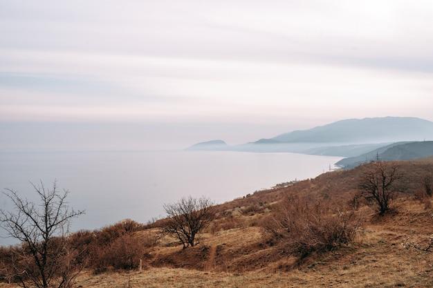 Costa otoñal con mar azul y tierra rocosa