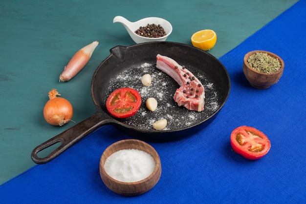 Costilla cruda en sartén negra con verduras y especias en mesa azul.