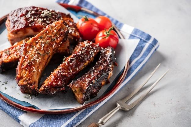 Costillas de cerdo asadas ahumadas en la placa. deliciosas costillas a la parrilla