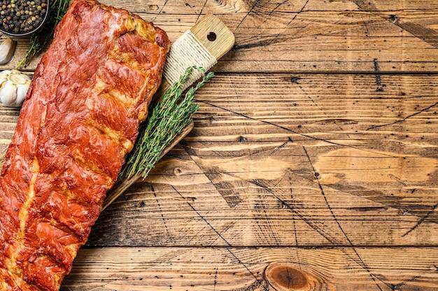 Costillas de cerdo a la barbacoa en una tabla de cortar con hierbas