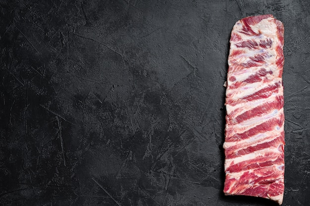 Costillas de cerdo crudas frescas. fondo negro. vista superior. espacio para texto