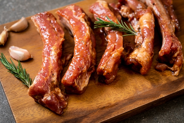 Costillas de cerdo crudas frescas listas para asar con ingredientes sobre tabla de madera