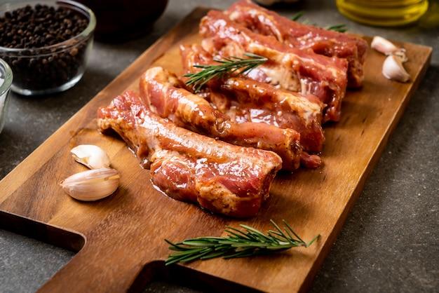 Costillas de cerdo crudas frescas listas para asar con ingredientes