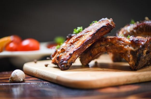 Costillas de cerdo a la parrilla con salsa de tomate y especias de hierbas servidas en la mesa