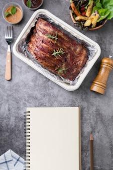 Costillas de cerdo a la parrilla con verduras y salsas en una mesa drak