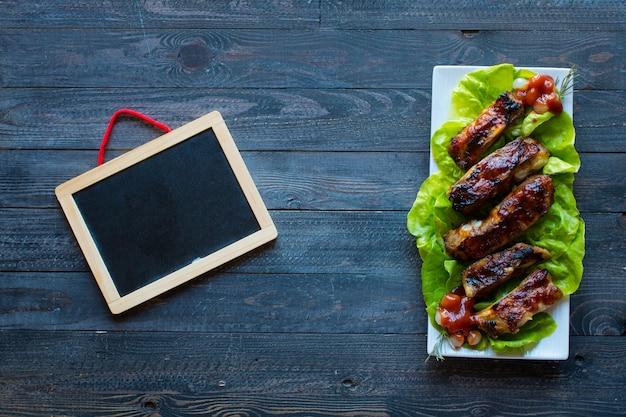 Costillas de cerdo a la parrilla con verduras sobre un fondo de madera; espacio libre antes del texto.