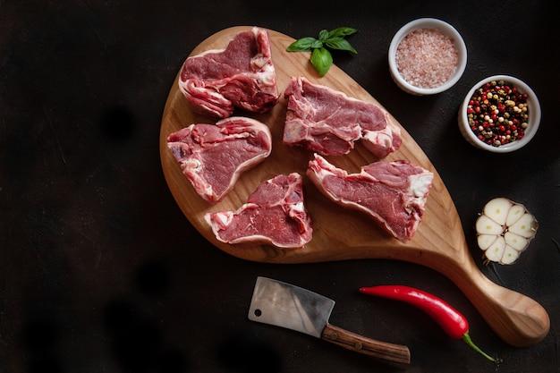 Costillas y condimentos frescos crudos de la carne del cordero en tabla de cortar de madera.