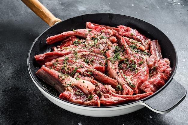 Costillas de cordero crudas frescas marinadas con tomillo y menta en una sartén
