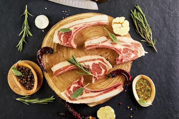 Costillas de cordero crudas con ingredientes para cocinar: sal, pimienta, aceite de oliva y hierbas sobre un soporte de madera. vista superior