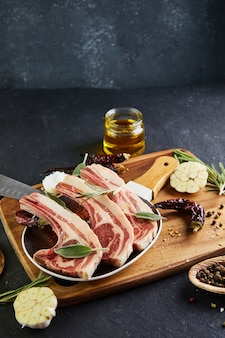 Costillas de cordero crudo con ingredientes para cocinar sal, pimienta, aceite de oliva y hierbas en un plato