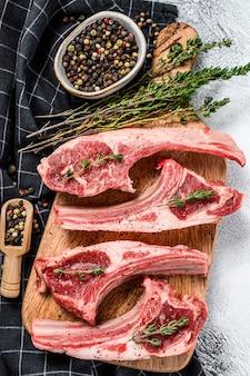 Costillas de cordero frescas crudas con pimienta y tomillo. carne orgánica fondo blanco. vista superior