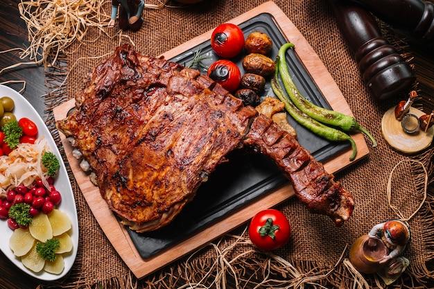 Costillas a la parrilla sobre la plancha de madera tomate pimiento patata vista superior