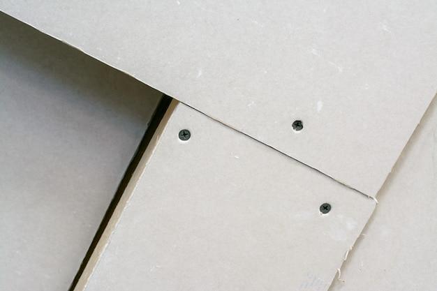 Costura entre dos hojas del panel de yeso con tornillos del techo suspendido moderno