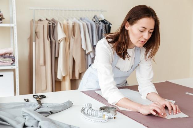 Costurera concentrada haciendo patrones