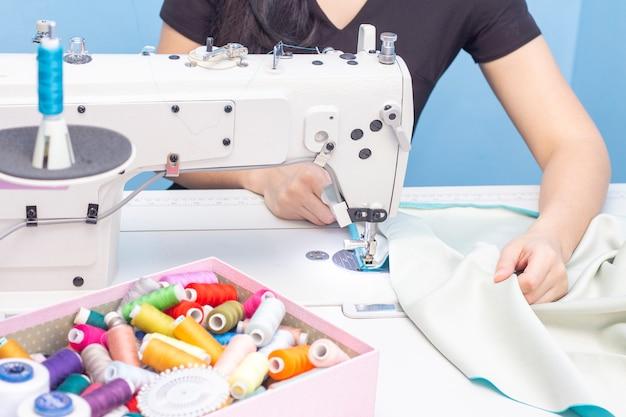 Costurera cosiendo en un primer plano de la máquina de coser. un conjunto de artículos para costura: hilos, agujas, alfileres, tijeras, cinta métrica, etc.