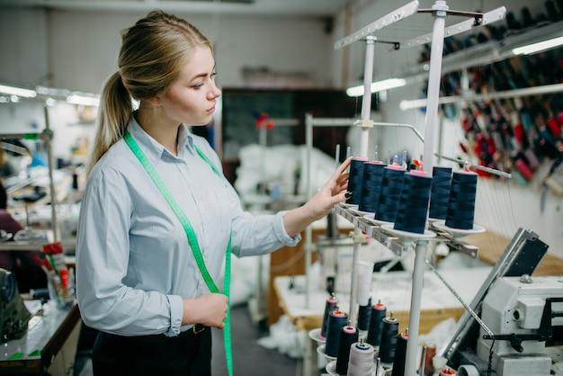 Costurera crea hilos negros en la máquina overlock, material de costura. sastrería o confección en fábrica de prendas de vestir